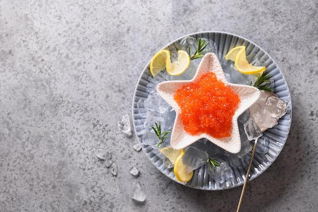 Rode kaviaar in kom in vorm van ster die met citroen en ijsblokjes op grijze steenlijst wordt gediend. ruimte voor tekst. bovenaanzicht. Premium Foto