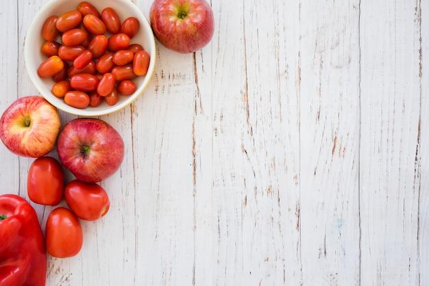 Rode kersentomatenkom; appel en paprika op witte gestructureerde achtergrond Gratis Foto