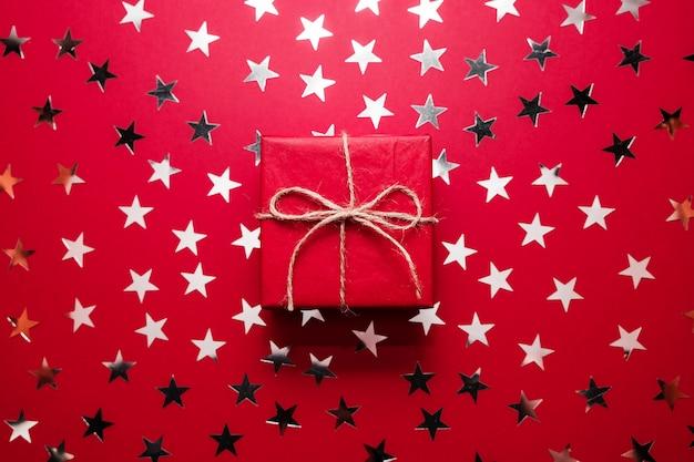 Rode kerst geschenkdoos met zilveren ster hagelslag op rode achtergrondkleur. plat leggen. Premium Foto