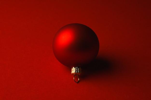 Rode kerstbal ligt op een rood oppervlak met schaduwen. hoge kwaliteit foto Premium Foto
