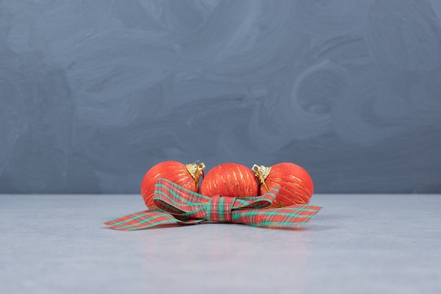 Rode kerstballen en lint op grijze achtergrond. hoge kwaliteit foto Gratis Foto