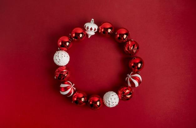 Rode kerstboom speelgoed decoratie opgemaakt als een ronde frame op een rode achtergrond met kopie ruimte. nieuwjaars wenskaart lay-out. minimale stijl. plat leggen. Premium Foto