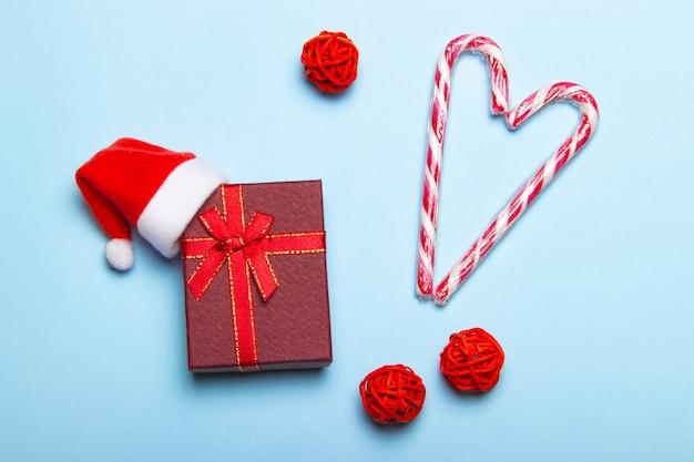Rode kerstcadeau op een blauwe achtergrond. geschenk en snoep. kerst lay-out. vakantie. nieuwjaar. geschenken. Premium Foto