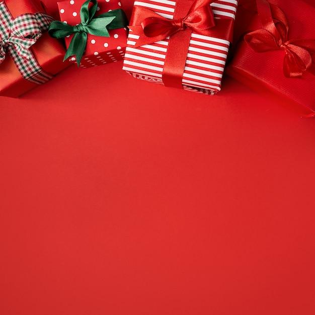 Rode kerstcadeautjes op rood Gratis Foto
