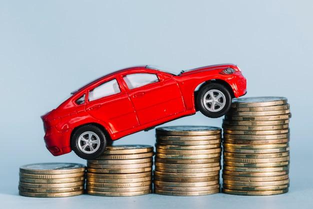 Rode kleine auto die over de toenemende muntstapel berijdt tegen blauwe achtergrond Gratis Foto