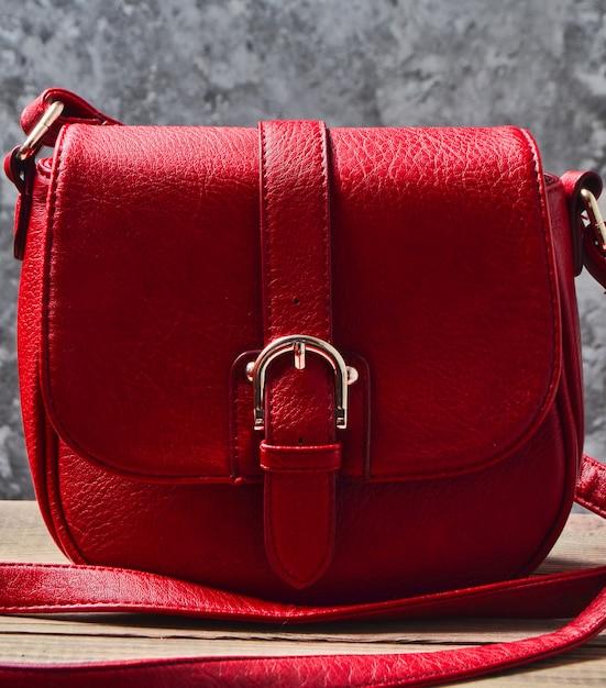 Rode lederen tas op een houten plank tegen een grijze betonnen muur. Premium Foto