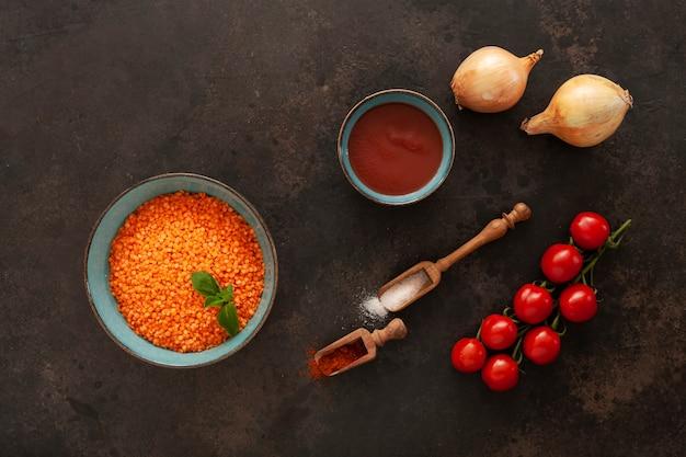 Rode linzen, tomaten, ui, tomatenpuree en kruiden, ingrediënten voor het koken van roomsoep Premium Foto