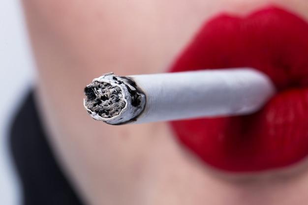Rode lippen die een sigaret dicht omhoog roken Premium Foto