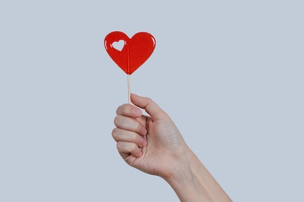 Rode lolly in de vorm van een hart in een vrouwelijke hand, op een grijze muur. Premium Foto