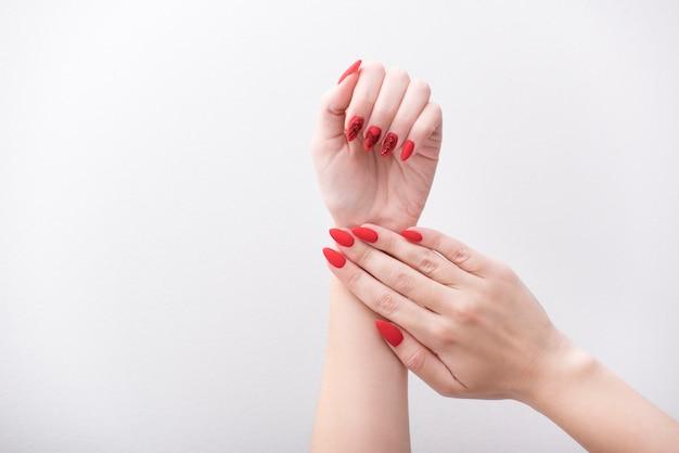 Rode manicure met een patroon. vrouwelijke handen op een wit Premium Foto