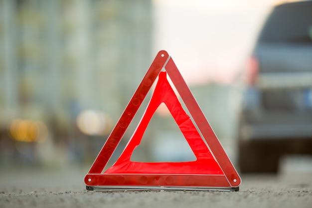 Rode nood driehoek stopbord en gebroken auto op een stad straat. Premium Foto