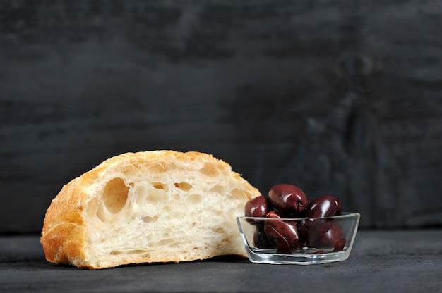 Rode olijven in een glazen plaat en ciabatta Premium Foto