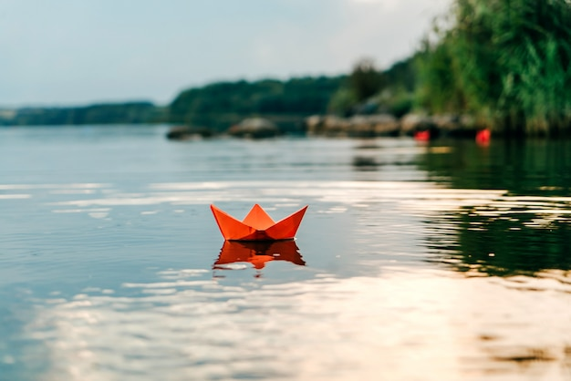 Rode papieren origami boot drijft op het wateroppervlak en reflecteert zichzelf Premium Foto