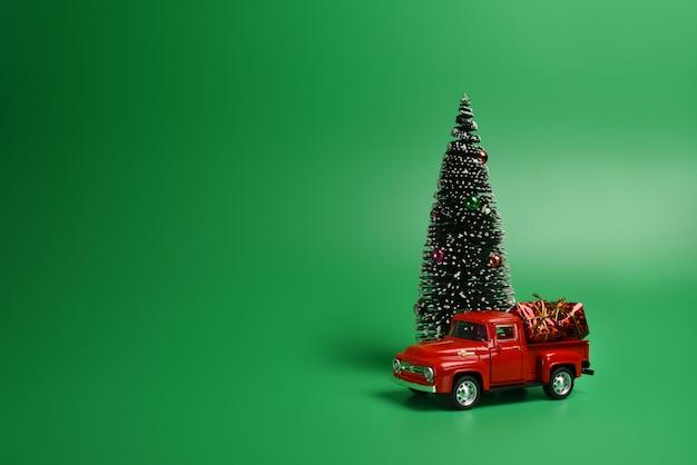 Rode pick-up met een kerstboom in de rug op een geïsoleerde groene achtergrond. Premium Foto