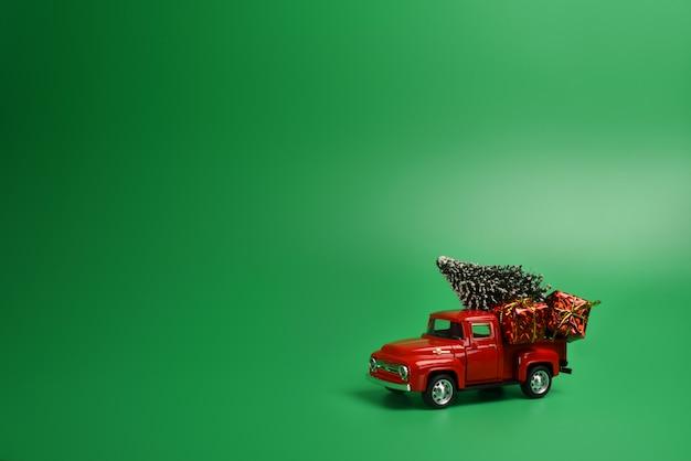 Rode pick-up met een kerstboom in de rug op een geïsoleerde groene achtergrond Premium Foto
