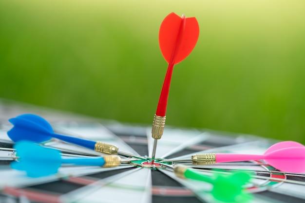 Rode pijlpijlen die in het doelcentrum raken van dartboard met groene aardachtergrond. Premium Foto