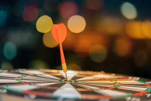 Rode pijltjepijl die in het doelcentrum van dartboard met achtergrond van stads de lichte bokeh raken. Premium Foto