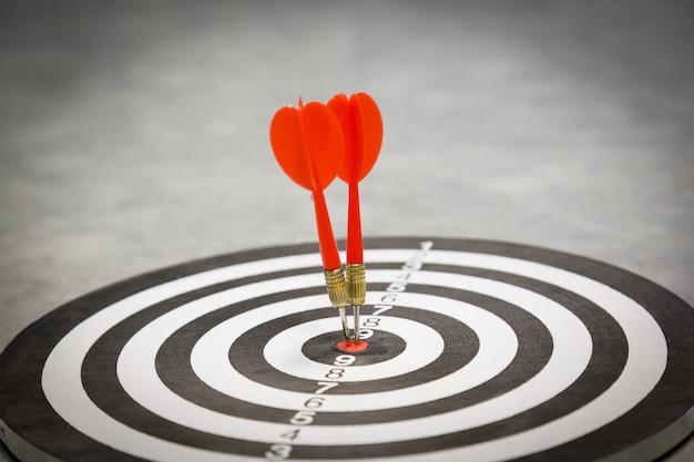 Rode pijltjepijl die in het doelcentrum van dartboard op bullseye met zonlicht uitstekende stijl raken Premium Foto