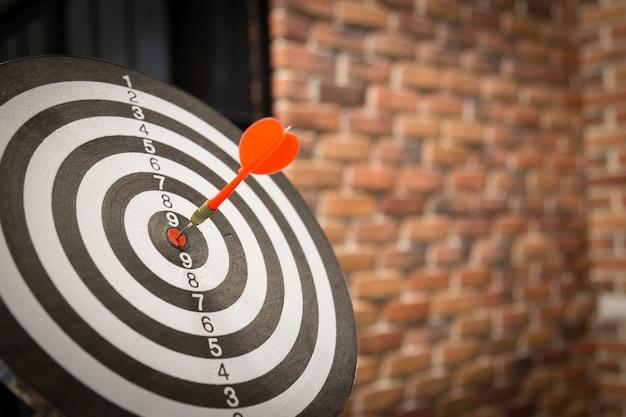 Rode pijltjepijl die in het doelcentrum van dartboard op bullseye met zonlicht vintage stijl raakt. Premium Foto