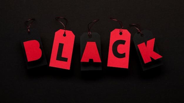 Rode prijskaartjes op donkere achtergrond zwarte vrijdag concept Gratis Foto