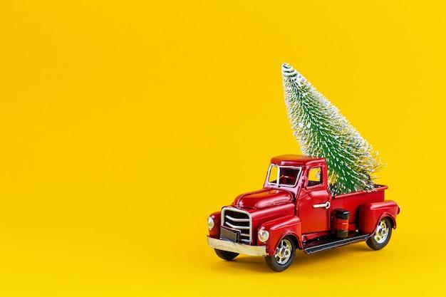 Rode retro stuk speelgoed vrachtwagen met kerstboom op vrachtwagenlichaam op gele muur. levering, kerstmis, nieuwjaar concept. vintage speelgoed modelauto met kerstboom kopieer de ruimte. Premium Foto