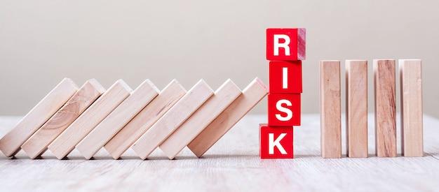 Rode risk-kubusblokken stoppen vallende blokken op tafel. vallen bedrijfs-, planning-, management-, oplossing-, verzekerings- en strategieconcepten Premium Foto