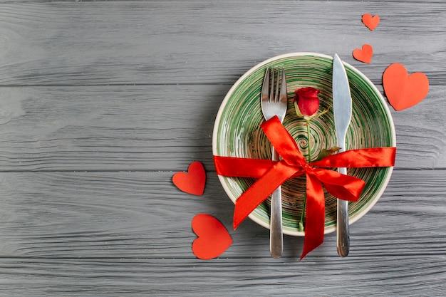 Rode roos met bestek op kom Gratis Foto