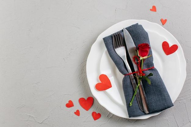 Rode roos met bestek op lichte plaat Gratis Foto