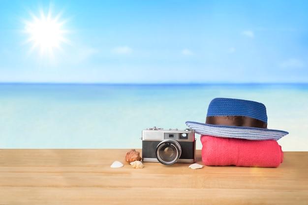 Rode roze toren, blauwe hoed, oude vintage camera en schelpen over houten tafel op zonneschijn blauwe hemel en oceaan achtergrond Gratis Foto