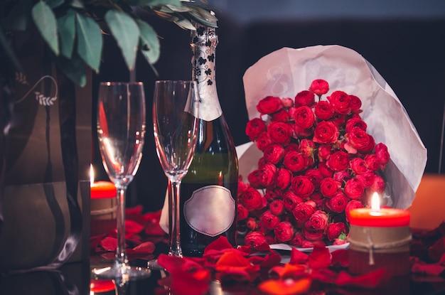 Rode rozen, twee glazen, fles champagne en kaars op tafel Gratis Foto