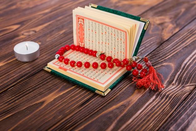 Rode rozentuinparels binnen een open islamitisch heilig kuranboek met aangestoken kaars op houten oppervlakte Premium Foto