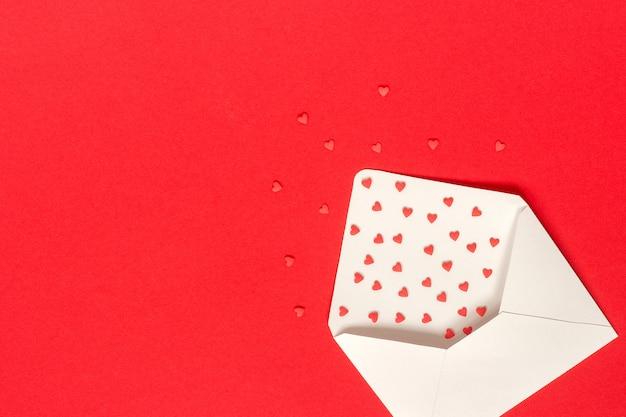 Rode snoepjes bestrooit snoep harten vliegen uit witboek envelop op rode achtergrond. Premium Foto