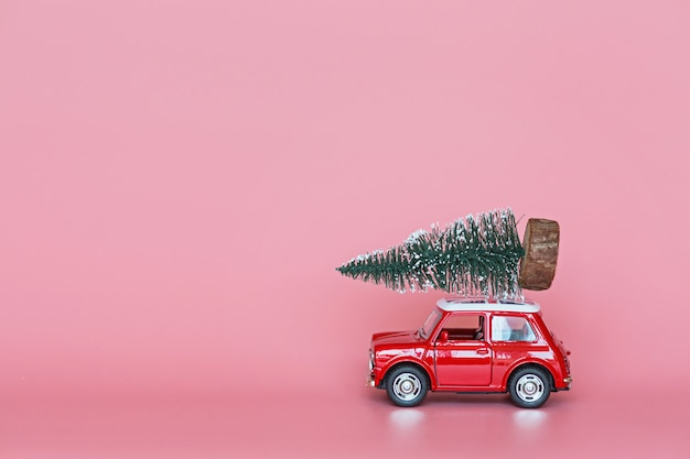Rode speelgoedauto met een kerstboom op het dak op roze Premium Foto