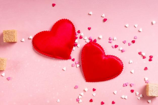 Rode stoffenharten, suikerklontjes, confetti op roze achtergrond. valentijnsdag 14 februari liefde minimaal concept Premium Foto