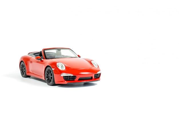 Rode stuk speelgoed auto, die op witte achtergrond wordt geïsoleerd Premium Foto