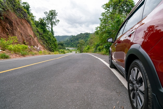 Rode suv-auto op asfaltweg met berg groen bosvervoer Premium Foto