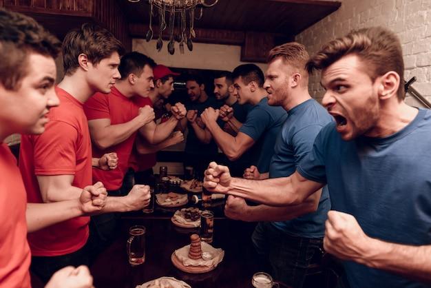 Rode teamfans en blauwe teamfans vechten. Premium Foto
