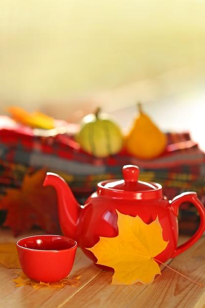 Rode theepot met een kopje thee, geruite sjaals en geel herfstblad Premium Foto