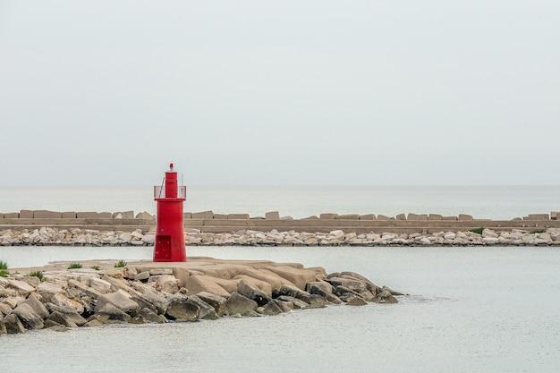 Rode toren die zich rond het strand onder een heldere blauwe hemel bevindt Gratis Foto