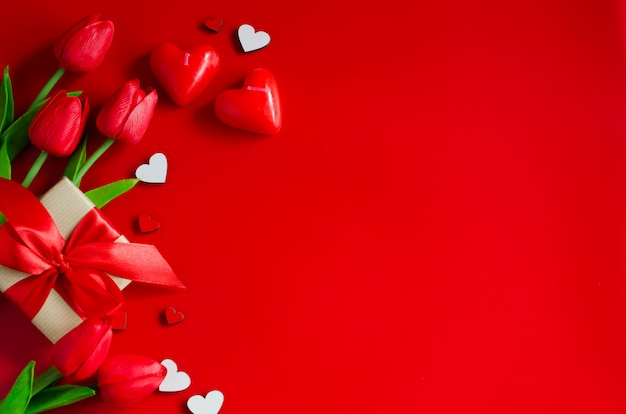 Rode tulpen, geschenkdozen en houten harten op rode achtergrond. wenskaart voor valentijnsdag. Premium Foto