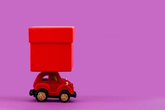 Rode velours speelgoedauto met een rode geschenkdoos voor kerstmis, nieuwjaar, valentijnsdag, verjaardag op een lichtpaars met copyspace Premium Foto