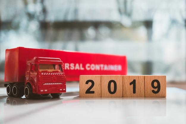 Rode vrachtwagencontainer met houten blok 2019 gebruikend voor logistiek en bedrijfsconcept Premium Foto