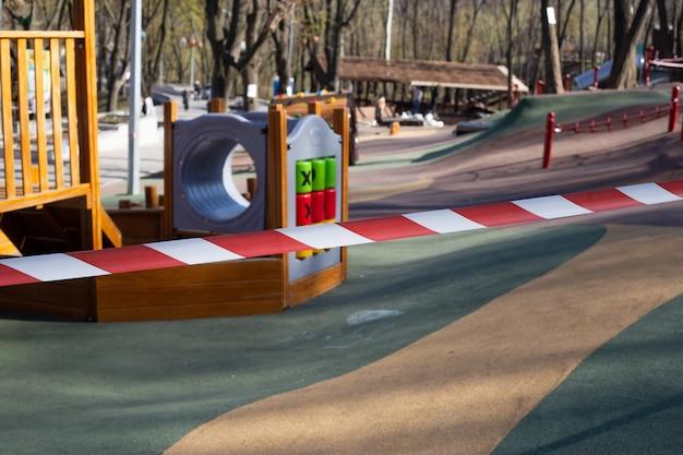 Rode waarschuwingsband op gesloten kinderspeelplaats, vanwege covid-19 quarantaine, gesloten quarantainespeeltuin. Premium Foto