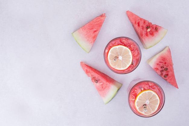 Rode watermeloenplakken met twee glazen sap Gratis Foto