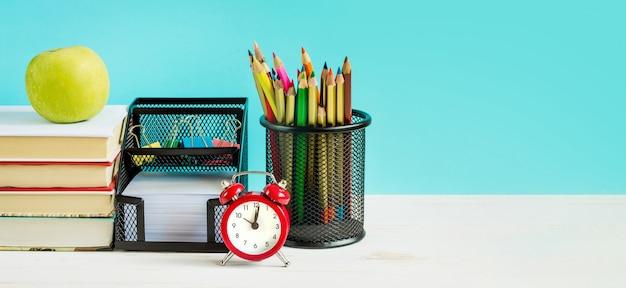 Rode wekker, appel, kleurpotloden, boeken op een blauwe achtergrond Premium Foto