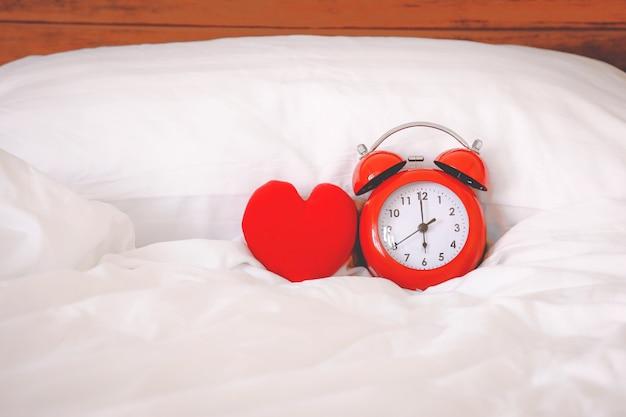 Rode wekker en rode hartvorm op het bed thuis Premium Foto