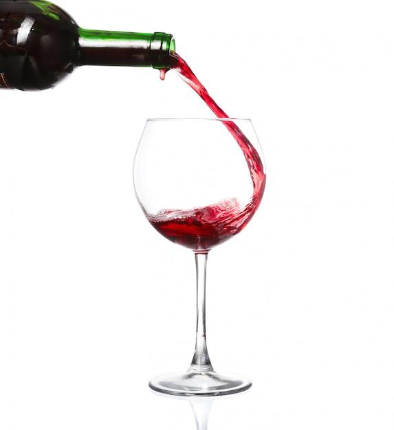 Rode wijn die in wijnglas gieten dat op wit wordt geïsoleerd Premium Foto