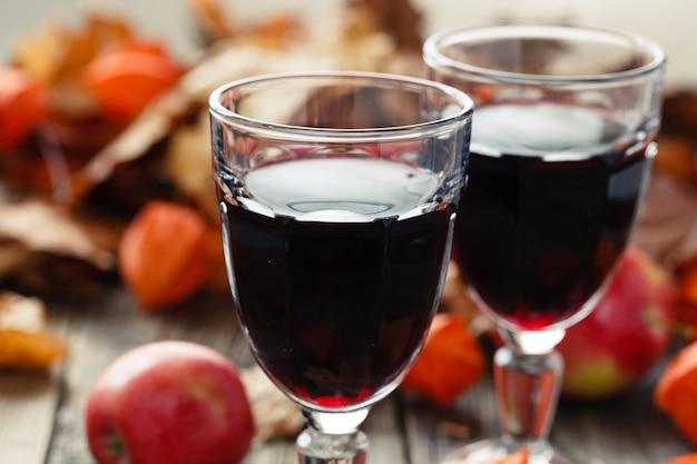 Rode wijn in glazen op lijst in dalingsblad Premium Foto