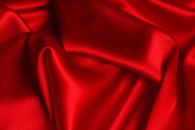 Rode zijde of satijn luxe stof textuur kan als abstracte achtergrond gebruiken. bovenaanzicht. Premium Foto