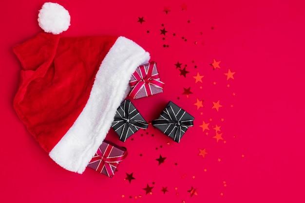 Rode, zwarte geschenkdozen in kerstman hoed op donkerrode achtergrond Premium Foto
